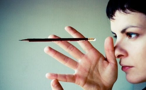 A woman looking at a suspended pencil.
