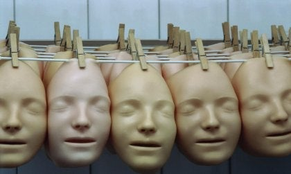 Realistic face masks hanging from a clothesline.