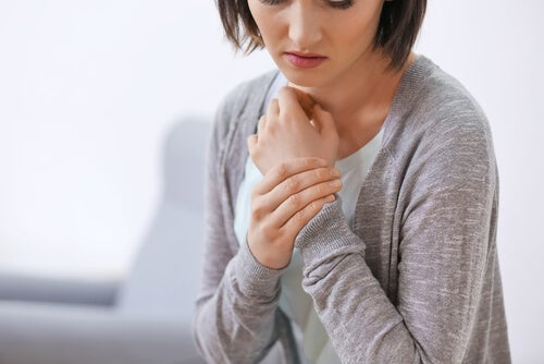 A woman rubbing her wrist.