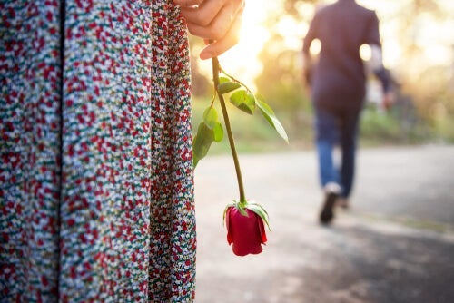 A man walking away from a woman holding a rose.