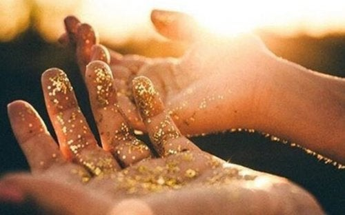 A pair of hands powdered in golden dust.