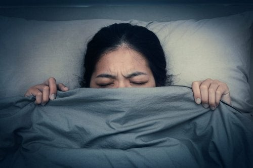 A woman hiding under the sheets.