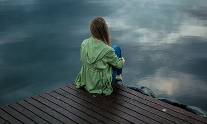 A woman at a dock in front of the sea. It's time to be happy.