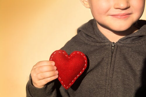 A little boy holding a heart.
