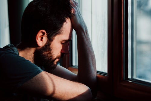 A man with anxiety leaning against the window.