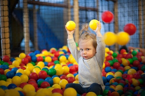 A child playing in a ballpit.
