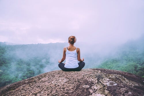 A woman meditating on top of a mountain.