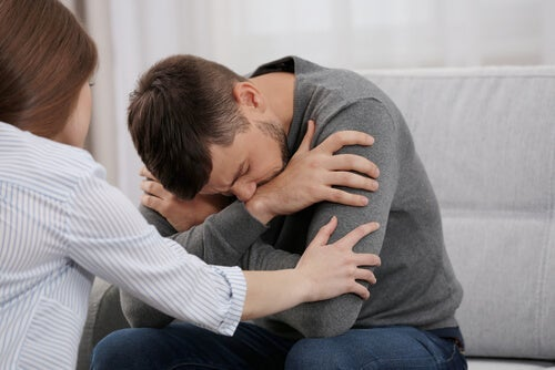 A woman trying to console a man.