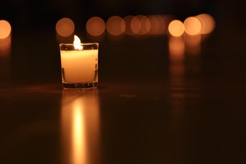 A small lit candle in the dark.