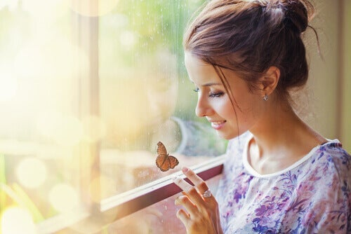 A woman smiling at a butterfly on the window.
