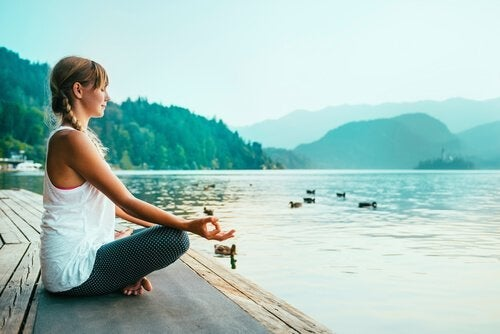 A woman meditating by the water.
