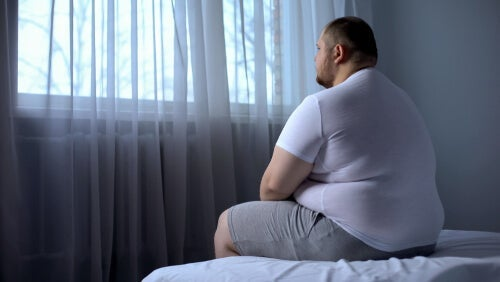 An obese man sitting on a bed.