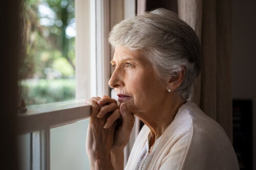 An elderly woman looking out the window.
