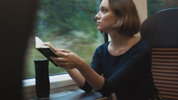 A woman reading on a train.