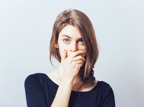 A woman covering her mouth symbolizing self-censorship.