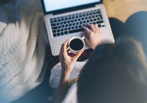 A woman drinking coffee and working on her computer.