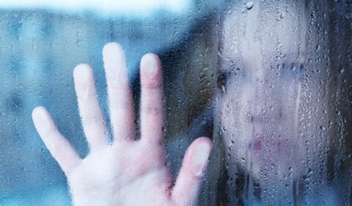 A woman with her hand on a rainy window.