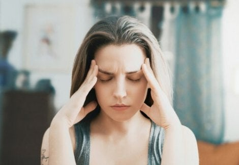 A woman with her hands on her head thinking about ego-depletion theory.