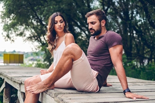 A man and a woman sitting on a dock.