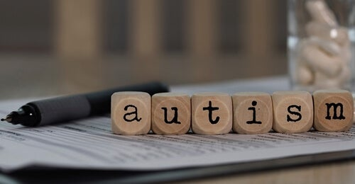 "Blocks on paper spelling out the word ""autism""."
