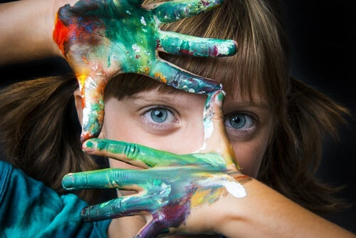 A little girl with painted hands framing her eye.