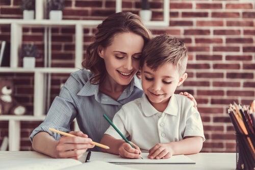 A woman helping a child write.