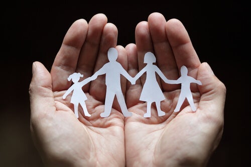 A paper cut-out of a family in someone's hands.