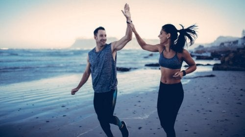 A man and woman high-fiving each other while jogging.