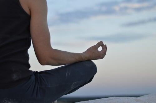 A man sitting cross-legged meditating.
