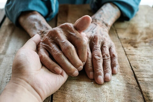 An old person's hand holding a younger person's hand.