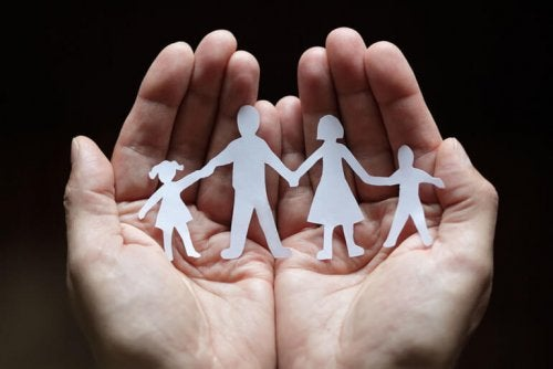 A paper family in a hand.
