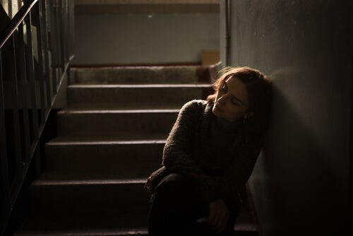 A sad woman leaning against the wall on a stairwell.