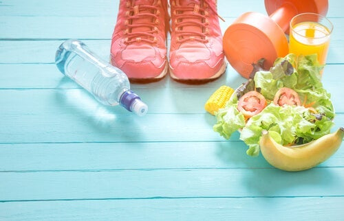 Healthy food, tennis shoes, a dumbbell, and a bottle of water on a blue floor.