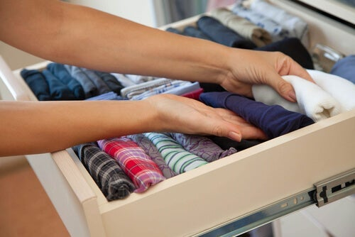 A woman organizing her folded shirts in a drawer.