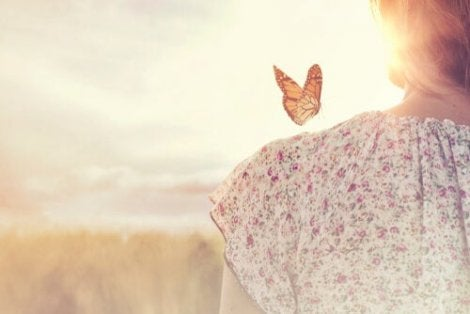 A woman standing in front of a setting sun with a butterfly on her shoulder.