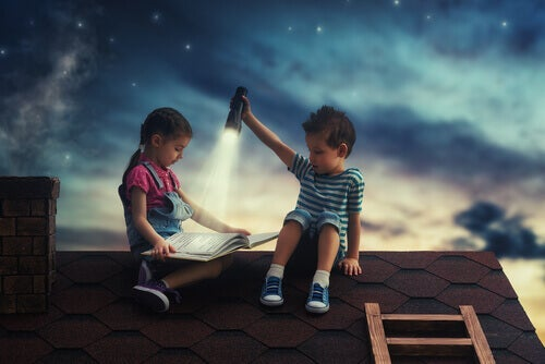 A boy holds a flashlight so a girl can read on the roof.