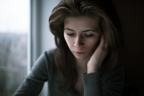 A woman resting her head on her hand, looking pensive.