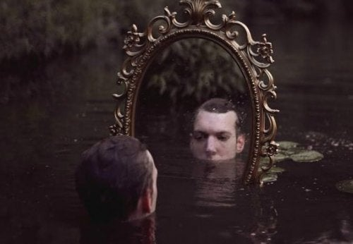 A man submerged in water looking in mirror.