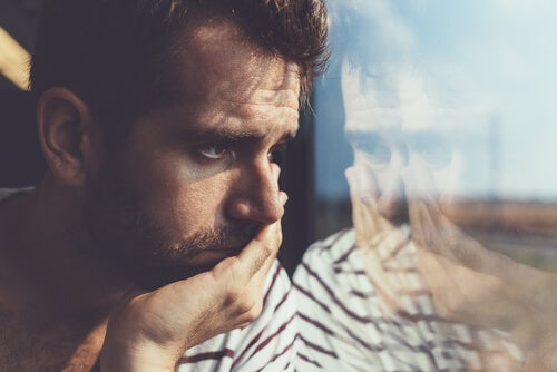 A man looking out a window feeling depressed.