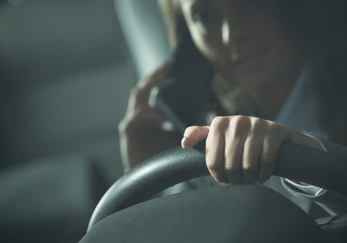 A woman driving while on her phone, at risk of getting in a car crash.