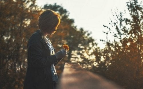 A woman looking at a flower at dusk.