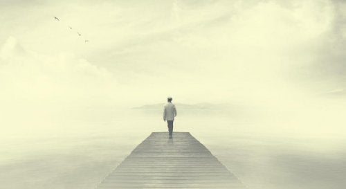 A person walking on a pier in the fog.