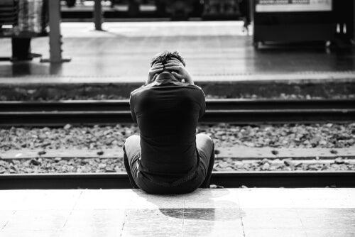 A boy sitting by train tracks.