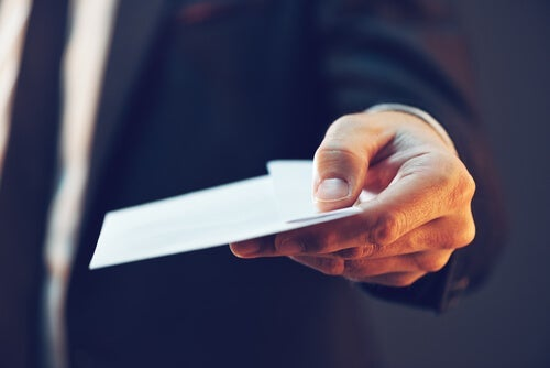 A person handing out an envelope.