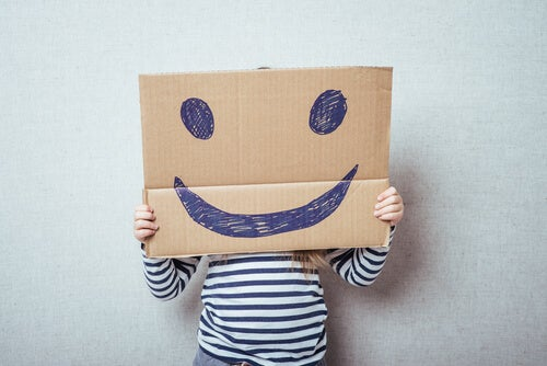 A child behind a smiley face board.