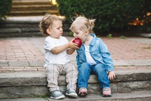 Two children sharing an apple.