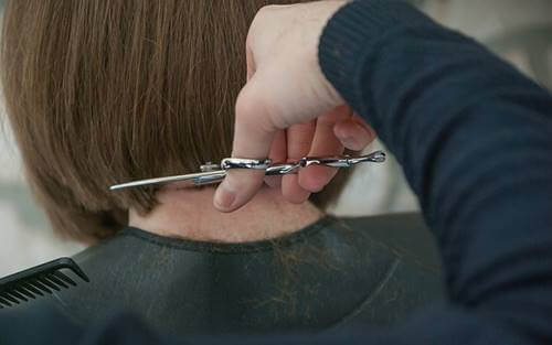 Someone cutting their hair.