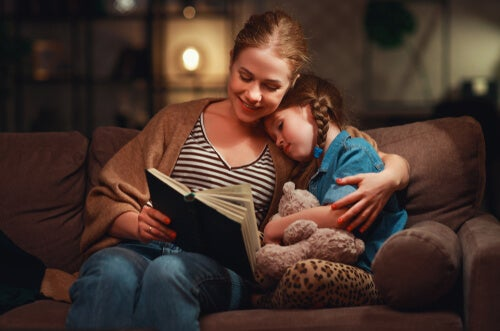 A mom on the couch reading with her daughter.
