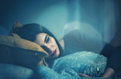 A sad woman lying in bed.