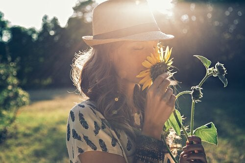 A woman smelling a sunflower.